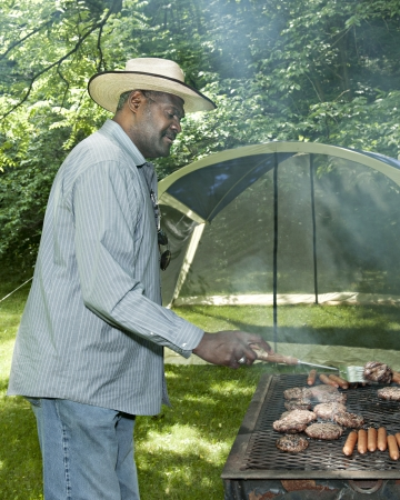 A mature African American man cooking hot dogs and hamburgers on an outdoor grill  photo