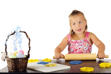 An adorable preschooler rolling out kiddie dough for cutting out with Easter-shaped cookie cutters Stock Photo - 17036266