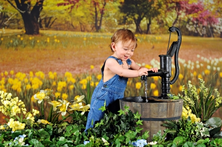 An adorable toddler standing among yellow daffodils playing with an old-fashioned waterpump Stock Photo - 17036301