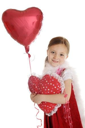 A beautiful elementary girl dressed in red with valentine beads and a fluffy white boa   She carries a lace-trimmed, heart shaped pillow and holds the string of a floating valentine balloon   On a white background Stock Photo - 17036225
