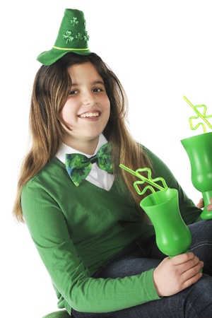 A happy preteen holding two green cups and dressed for St  Patrick Stock Photo - 17036307