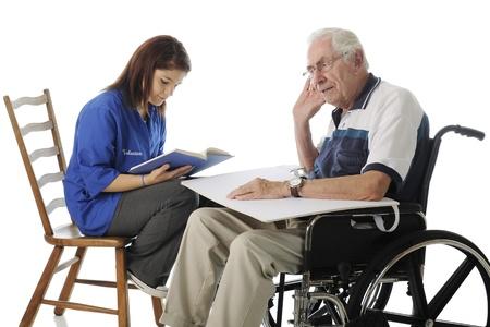 personas ayudando: Un adolescente atractivo voluntario lectura a un hombre con dificultades de audición superior en una silla de ruedas en un fondo blanco Foto de archivo