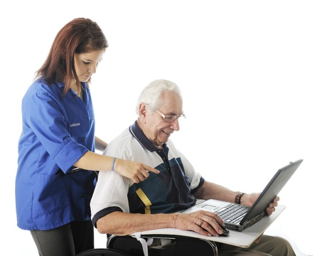 An attractive young volunteer assisting an elderly man with his computer   On a white background Stock Photo - 17036296
