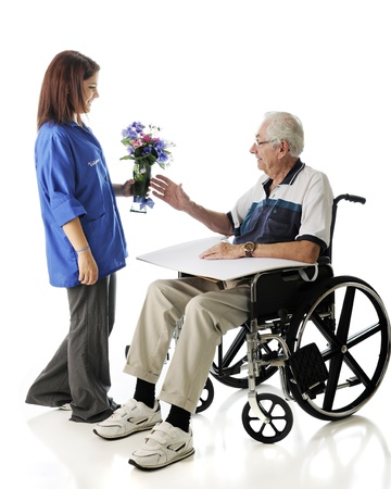An attractive teen volunteer delivering a vase of flowers to an elderly man in a wheelchair   On a white background Stock Photo - 17036267