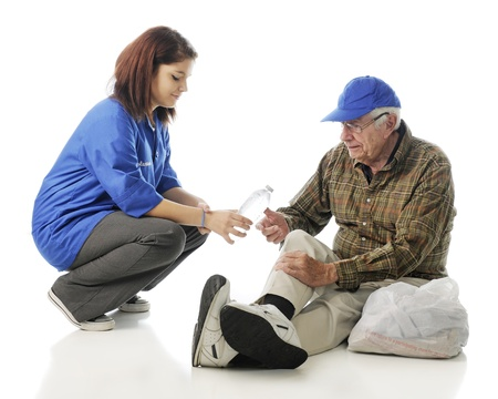 An attractive young volunteer passing out water to an elderly homeless man  On a white background  photo