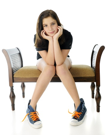 untied: A pretty preteen smiling at the viewer with her head resting on her hands   She sits on a bench with her knees together, feet apart, wearing shorts and oversized untied high-tops with neon laces   On a white background