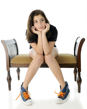 A pretty preteen girl wistfully sitting on a bench with her head propped by her hands, knees together and feet spread apart   She photo