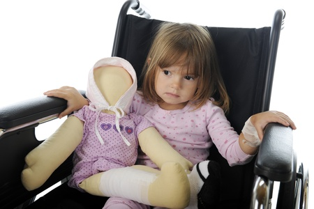 Closeup image of a sad little girl sitting in a wheelchair in her pajamas   She has a doll with bandages like hers Imagens - 17036329