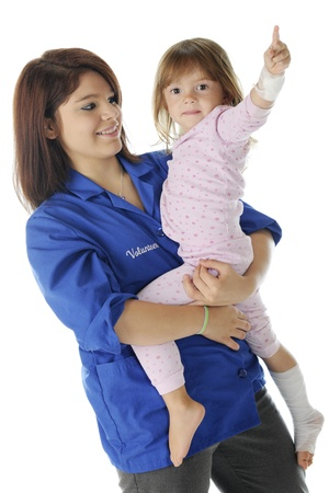 A pretty teen volunteer happily holding an injured little girl   The child wears pink pajamas and has an arm and leg wrapped in bandages   On a white background Stock Photo - 17036306