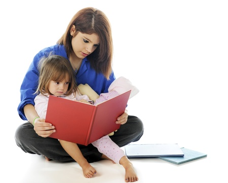 A young hospital volunteer and preschooler reading a book together   On a white background  photo