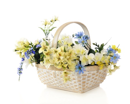 A white woven basket filled with beautiful pastel flowers.  Isolated on white. Stock Photo - 17039641