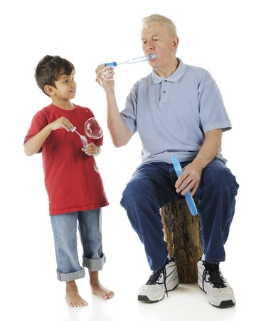 A barefoot preschooler holing a bottle of bubble-blower happily watches how his grandpa makes them happen.  On a white background. Stock Photo - 17036271