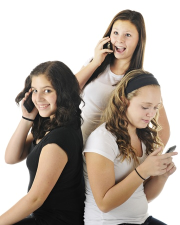 Three young teens using technology to communicate with other friends.  On a white background. Stock Photo - 17036229
