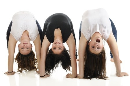 Three tween girls doing backbends together.  The first is content, the second smiles, the third is making a goofy face.  On a white background. Stock Photo - 17036270