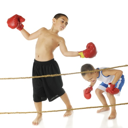 agachado: Un niño de primaria bopping su hermano pequeño con los guantes de boxeo. En un fondo blanco. Foto de archivo