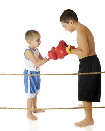 Two young fighters looking at each others with their boxing-gloved fists together behind ropes, ready to begin a fight.  Both have black eyes, are wearing shorts and are barefoot.  On a white background.