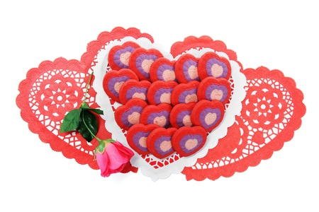 Multiple heart shaped cookies arranged on red and whiteValentine doilies, with a pink rose on the side.  On a white background. Stock Photo - 17039639