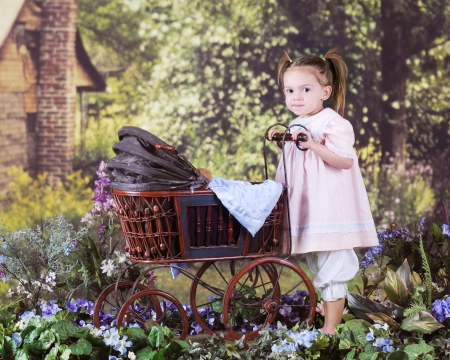 A beautiful preschooler pushing an antique doll buggy in a rustic, rural setting. Stock Photo - 17147962