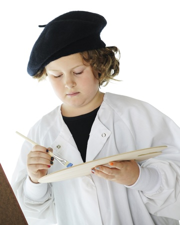 Closeup image of a serious elementary artist selecting colors from her paint palette.  On a white background. Stock Photo - 17147960