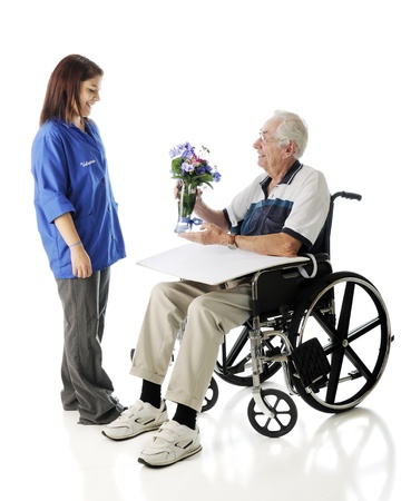 An elderly man in a wheelchair happily receives flowers from an attractive teen volunteer.  On a white background.