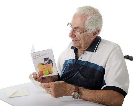 Closeup image of an elderly man reading a get well card while sitting in his wheelchair.  On a white background. Stock Photo - 17165326