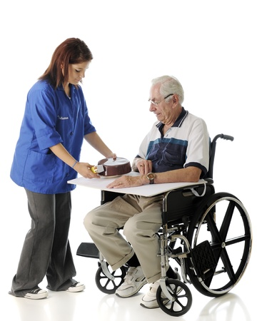 A pretty young volunteer passing a covered meal to a senior man in a wheelchair.  On a white background. photo