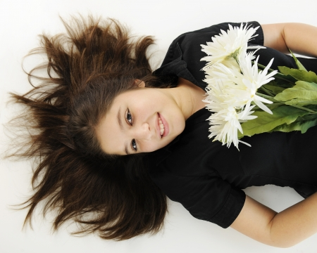An overhead view of a pretty preteen happily resting on her back with a bouquet of flowers. Stock Photo - 17165332