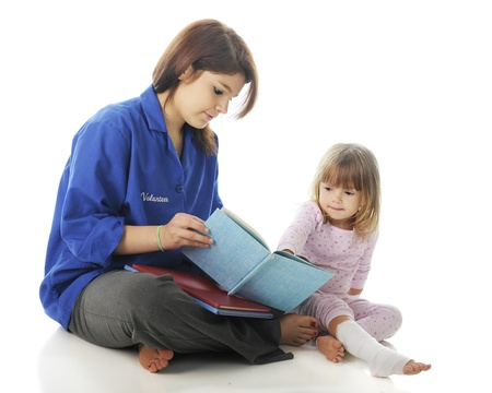 A pretty teen volunteer reading a story to an injured preschooler.  On a white background.