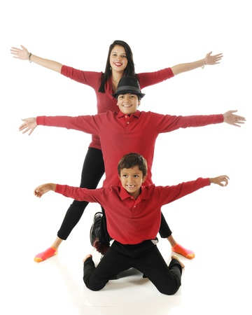 Three biracial siblings stacked behind each other with their arms outstretched, like a 3-headed bug with 6