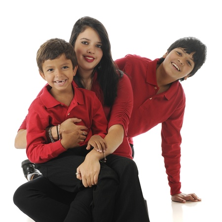 Three biracial siblings  Asian Indian   caucasian  on the floor    a preschool boy, teenage girl and their preteen brother   On a white background  photo