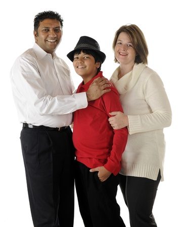 Standing portrait of a happy biracial family of three -- an Asian Indian dad, caucasian mom and their preteen son   On a white background  photo