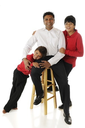 An Asian Indian man with his preschool and tween biracial sons   On a white background  photo