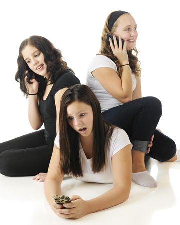 Three young teens relaxed together as they each communicate on their phones   On a white background   Focus on the girl on the floor  Stock Photo - 17165331