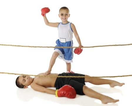 guantes de boxeo: Un boxeador feliz preescolar con p�rdida de un diente y el ojo negro levantando el pu�o en se�al de victoria mientras su hermano elemental edad yace vencido en el suelo sobre un fondo blanco Foto de archivo