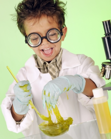 An adorable preschooler with wild hair and coke-bottle glasses delightedly  handling a bowl of yucky, green slime