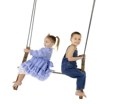 A preschool brother and sister swinging together on an antique 2-person pump swing   On a white background with plenty of space for your text  Stock Photo