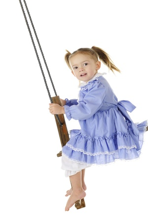 An adorable preschooler in an old fashioned dress and bloomers swinging high on an antique, wooden, self-pumping swing   On a white background Stock Photo - 17148005