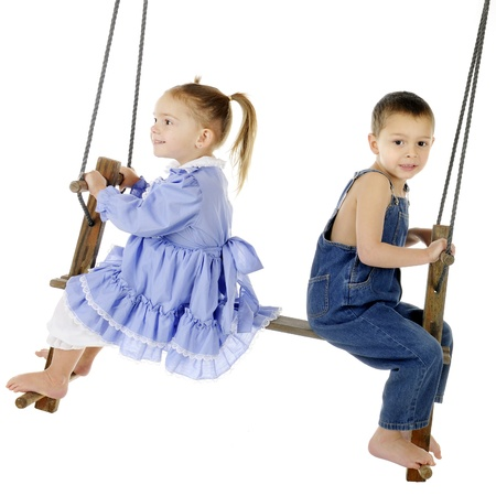 A preschool brother and sister swinging on an antique, 2-person, wooden pump-style swing   The girl is delighted, the boy worried   On a white background  Stockfoto