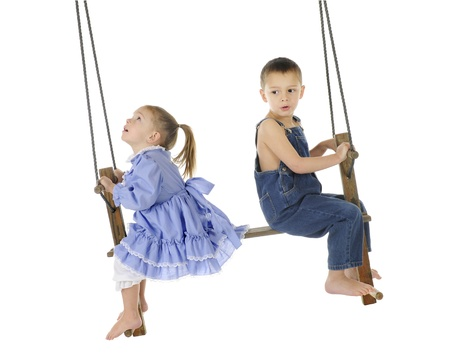 A preschool brother and sister playing on an old wooden, antique 2-person, pump swing together   The girl is looking up to the top of the ropes, while the brother looks back a bit worried   On a white background  Stockfoto