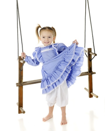 An adorable, barefoot preschooler lifting her pretty, old-fashioned dress, showing off her bloomers   She holds onto the ropes of an antique wooden, 2-person swing   On a white background Stock Photo - 17147940
