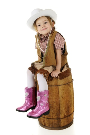 An adorable preschool cowbirl sitting pretty on an old barrel   On a white background  Stock Photo - 17147956