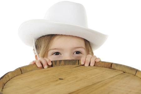 Closeup of an adorable preschool cowgirl with only her eyes peering over the top of an old wooden barrel   Room for your text on the barrel top   On a white background Stock Photo - 17155803