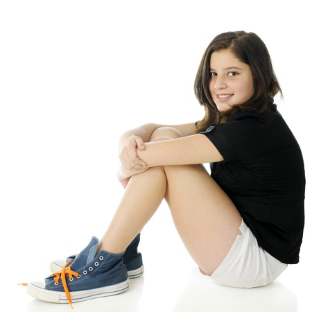 A pretty preteen looking at the viewer as she sits on the floor hugging her knees.  Shes wearing oversized high-top sneakers with bright laces.  On a white background. photo