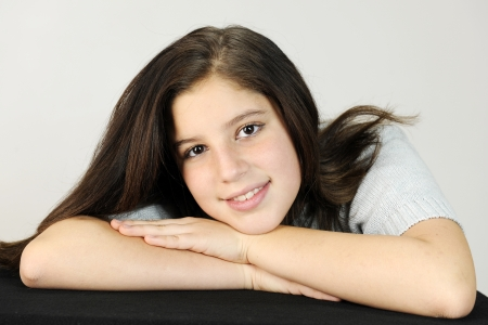 beautiful preteen girl: Close-up of a pretty preteen resting her head on her hands.