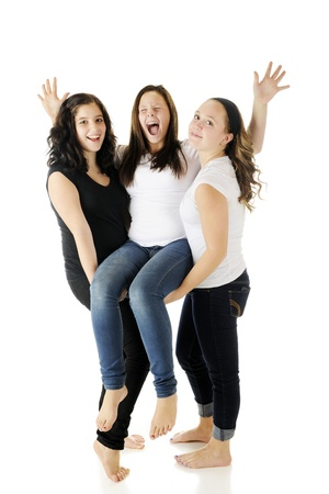 Two barefoot young teens listing another who's yelling like crazy with her victory.  On a white background. photo