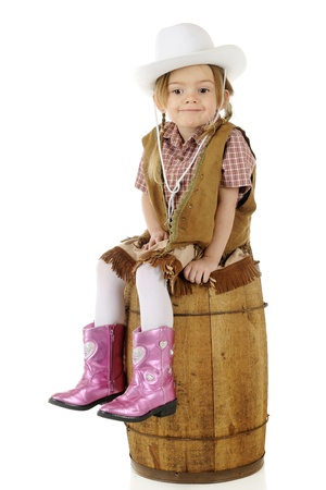 An adorable preschool cowgirl sitting on a rustic wood barrel looking smug.  On a white background. photo