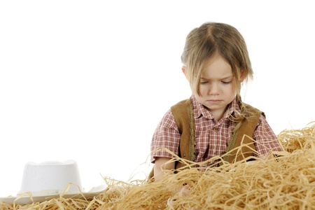 Head and shoulders of a very sad little cowgirl pouting behind a pile of straw with her hat off but nearby.  On a white background with space over her hat for your text. photo