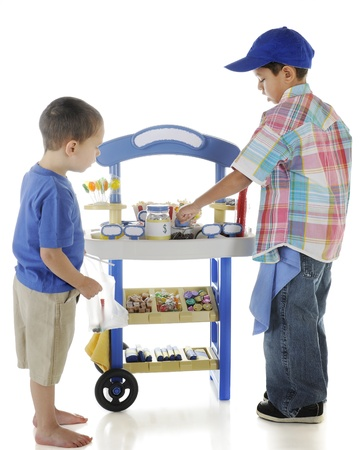 A young entrepreneur tending his candy stand while a preschool customer checks out the goods.  On a white background.