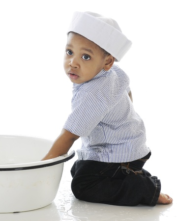 An adorable toddler wearing a sailor hat while playing in a tub of water.  On a white background. Stock Photo - 17509918