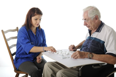 An attractive young volunteer playing Dominoes with an elderly man in a wheelchair.  On a white background. Stock Photo